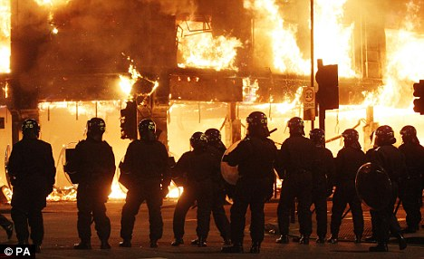 Flashback: Police line up during a firestorm of the London riots - and it has been revealed many of the perpetrators have re-offended