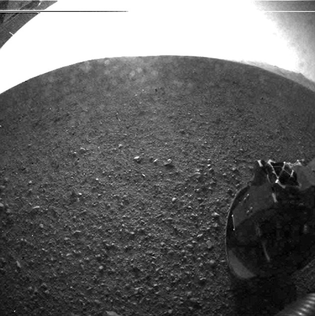 Curiosity later sent back the first high resolution picture of its landing site, showing one of its wheels on the martian surface. Colour images are expected later this week.