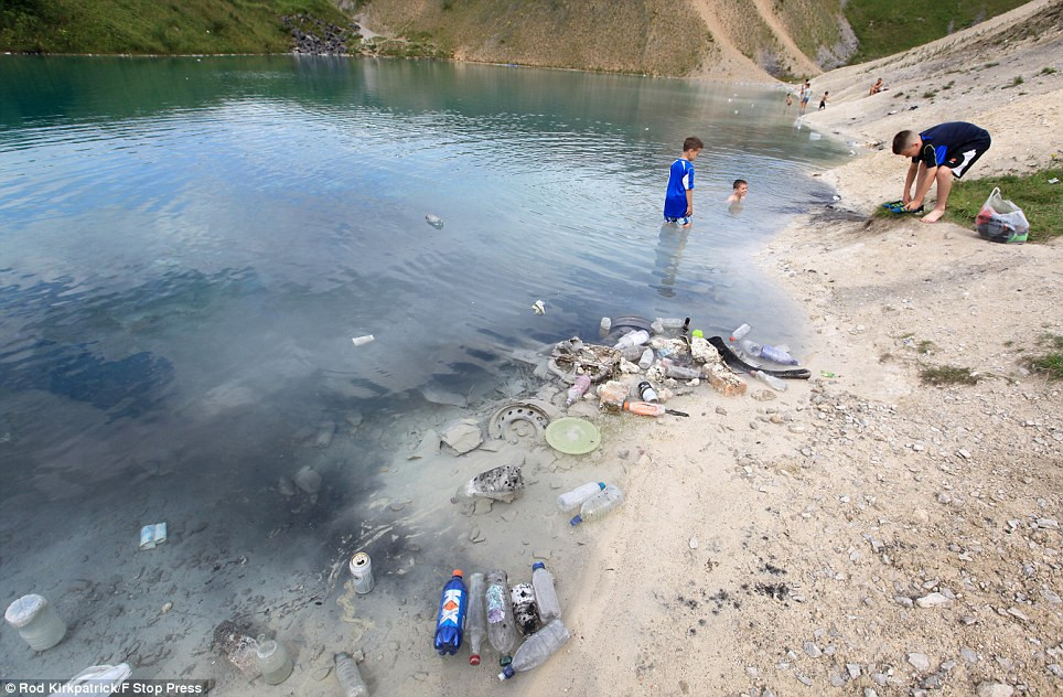 One youngster takes off his shoes as he prepares to join his friends in the poisonous waters. The council are looking at how they can have the area sealed off
