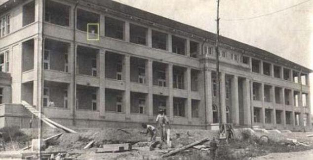 Deux hommes sont vu travailler à la rénovation de cette vieille et «vide» l'hôpital en 1918 -, mais sur le balcon de gauche, ils ne sont pas seuls