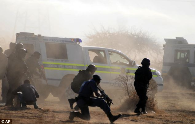 Gun battle: In the heat of the incident, dust flies and police take cover. Water cannon and tear gas had been fired at miners before police opened fire