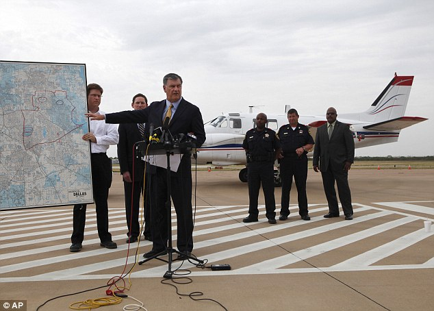 Plans: Dallas Mayor Mike Rawlings talks about aerial spraying to curb the spread of West Nile virus while standing before one of the Beechcraft aircraft being used to administer the insecticide