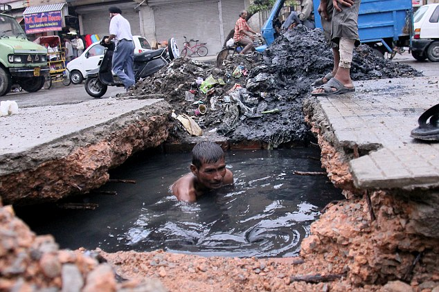 Wallowing in filth: Devi Lal, 43, works to unclog blocked drains in Delhi, India