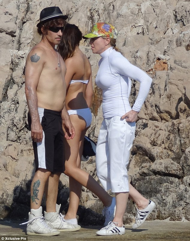 Covered up: Madonna ensured her pale skin was protected from the rays in the all-white get-up