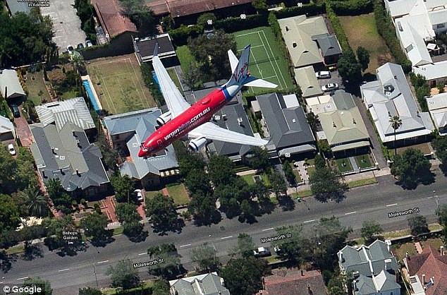 Captured mid-flight: The Virgin Airways plane flies over suburban tennis courts and swimming pools as it comes in to land