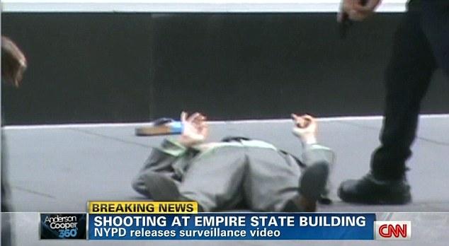Jeffrey Johnson se encuentra sometido en el suelo fuera del Empire State Building en la ciudad de Nueva York, mientras que un oficial de policía apunta con su arma