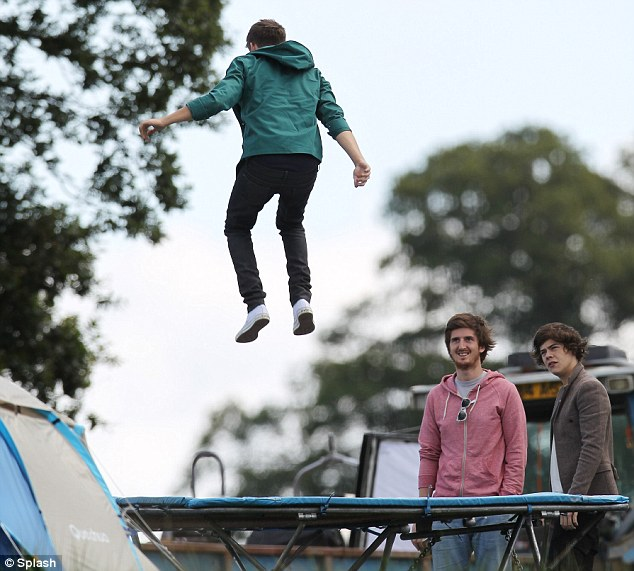 Jumping for joy: Niall warmed up for his performance on a trampoline, while Harry looked on