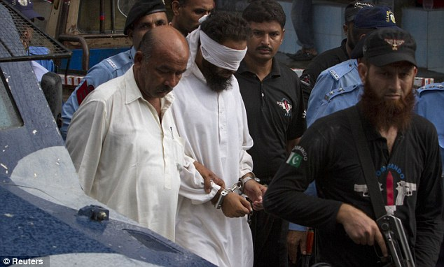 Police escort blindfolded Muslim cleric Khalid Jadoon as he is brought before a judge at a court in Islamabad today accused of framing the young girl