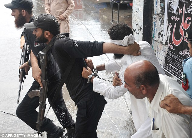 A Pakistani policeman reprimands Islamic cleric Hafiz Mohammed Khalid Chishti after he attempted to shout slogans upon his arrival at a court in Islamabad today
