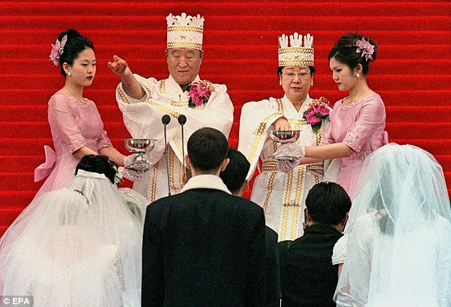 Blessing: Sun Myung Moon and his wife bless the brides and the grooms in a mass wedding ceremony at Chamsil Olympic Stadium in Seoul in 2000