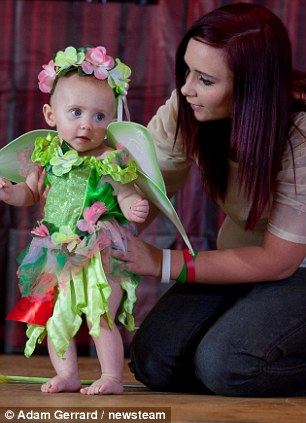 Little Chloe Graves, 7 months was helped on stage by her mother at the event where she wore a green fairy costume