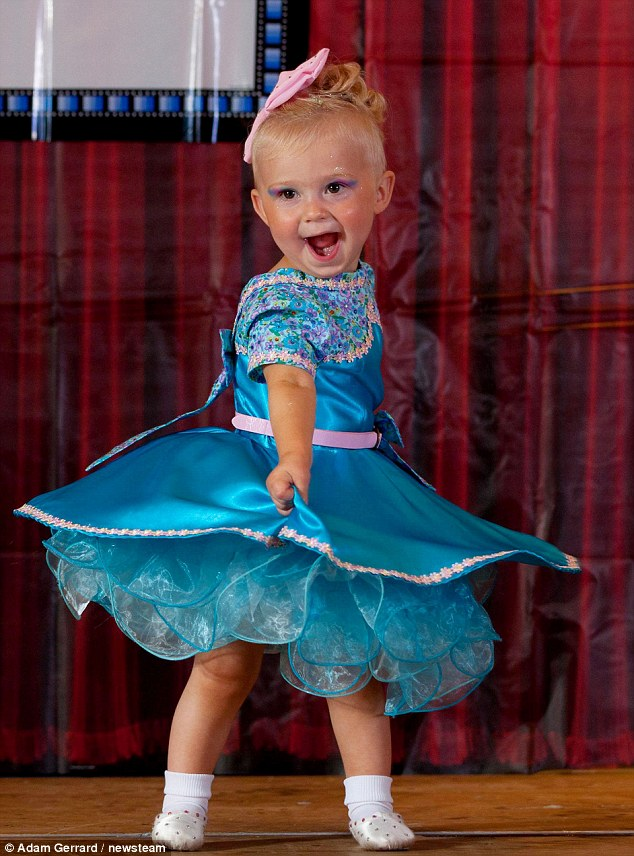 Twirl: Hollie Young, aged 20 months, smiles on stage at the Glitz Sparkle 2012 competition
