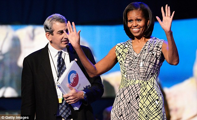 First lady Michelle Obama waves on stage during a sound check with stage manager David Cove during preparations for the Democratic National Convention at Time Warner Cable Arena