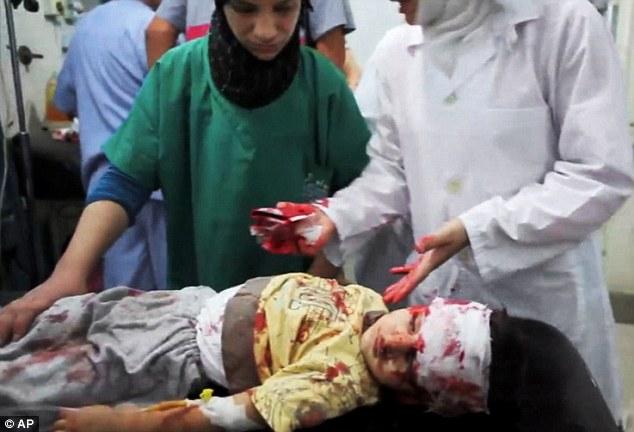 Sad: Syrian medics help a wounded child at the Dar al-Shifa hospital