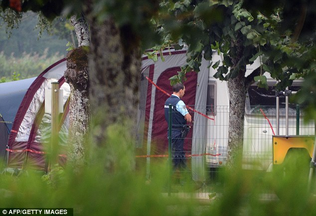 Gathering clues: A French gendarme stands guard near the caravan thought to have been used by the family