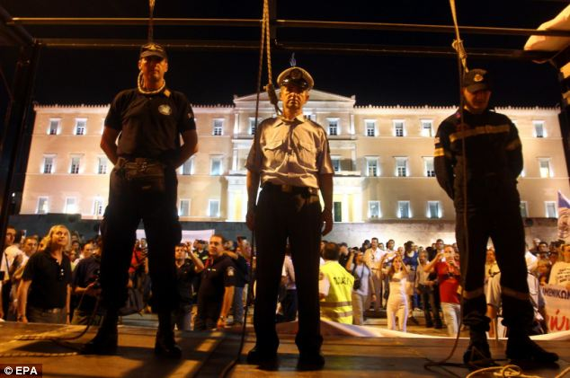 Protest: Uniformed members of the Greek security forces staged a mock hanging outside the country's parliament in Athens