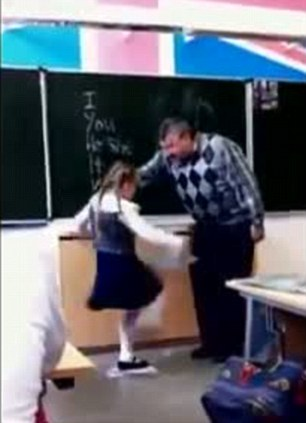 Take that: The little girl snaps and kicks out at the bullying teacher who is left crumpled up in pain