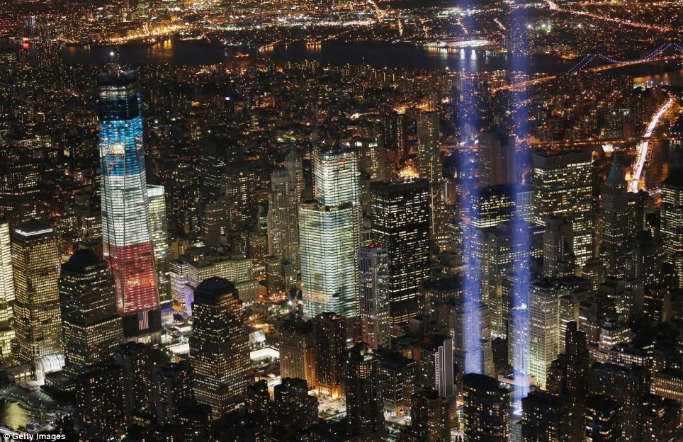 City of light: The 'Tribute in Light,' making where the towers of the World Trade Center once stood, rise into the night sky next two the site of the new One World Trade Center glows in red, white and blue
