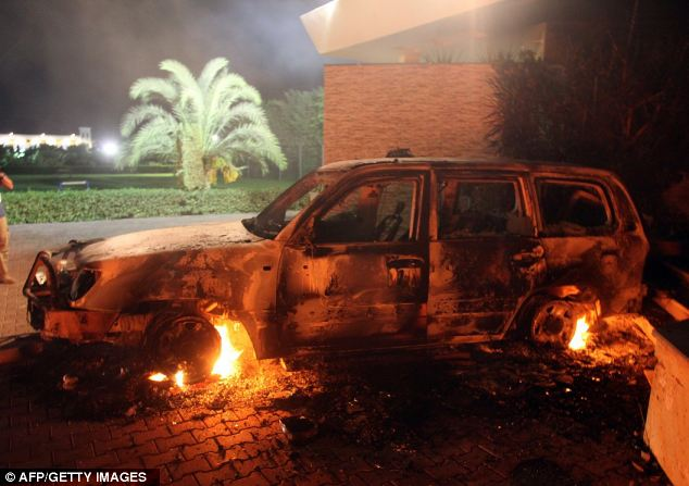 Violence: A vehicle sits smoldering in flames after being set on fire inside the US consulate compound in Benghazi late yesterday