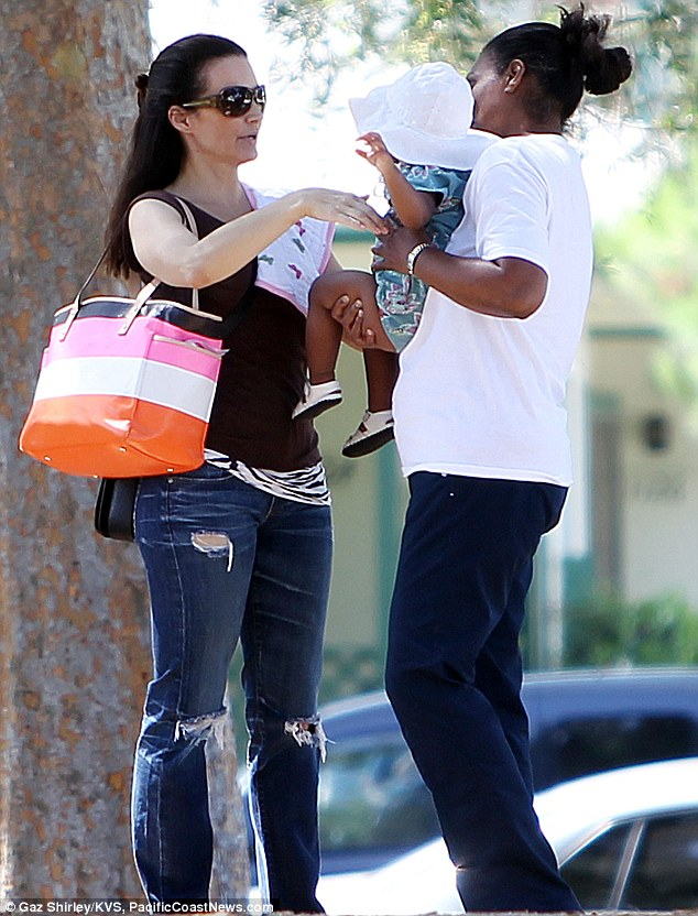 A helping hand: The actress was helped out by a nanny as she juggled her baby bag