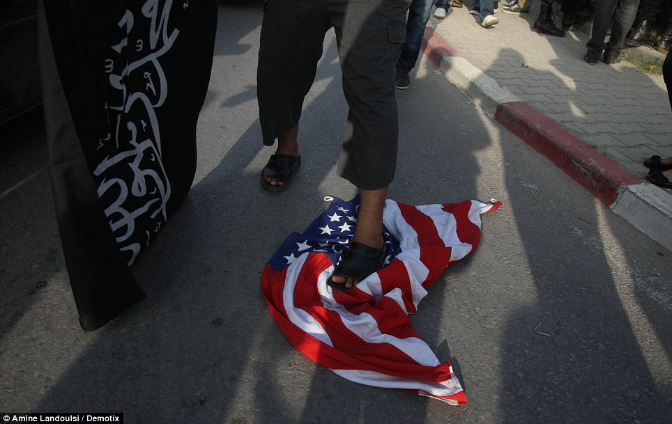 Anger: A Tunisian protester stomps on the American flag as Muslim countries erupted in protests over a low-budget anti-Mohammed film