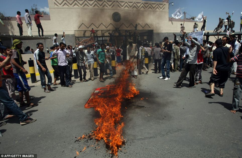 Blazing fire: Yemeni forces drive back the protesters as they approached the main gate of the mission