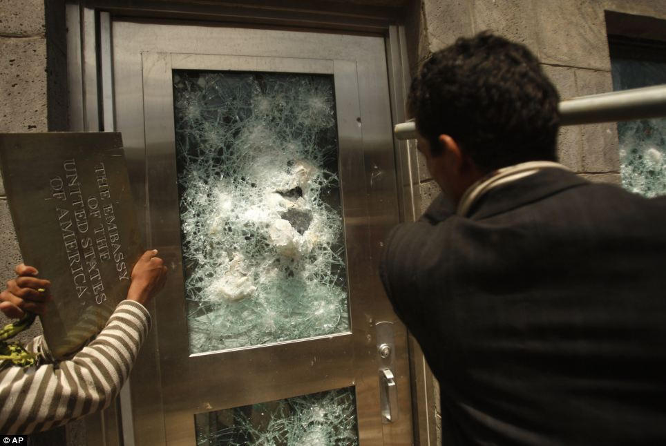 Chaos: Yemeni protestors break a door of the U.S. Embassy with a pole after ripping off the metal plaque