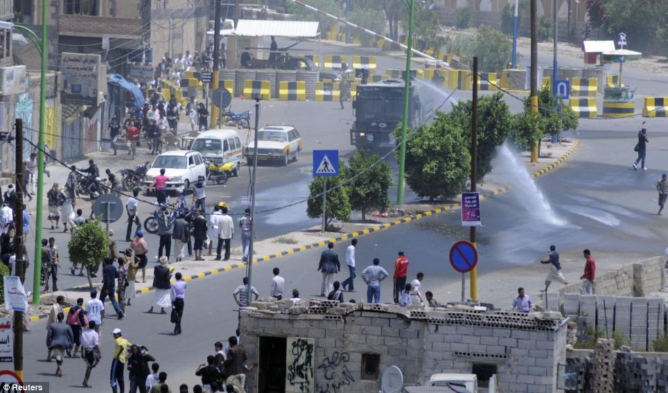 Control: Riot police made efforts to disperse protestors gathered outside the compound in Sana'a