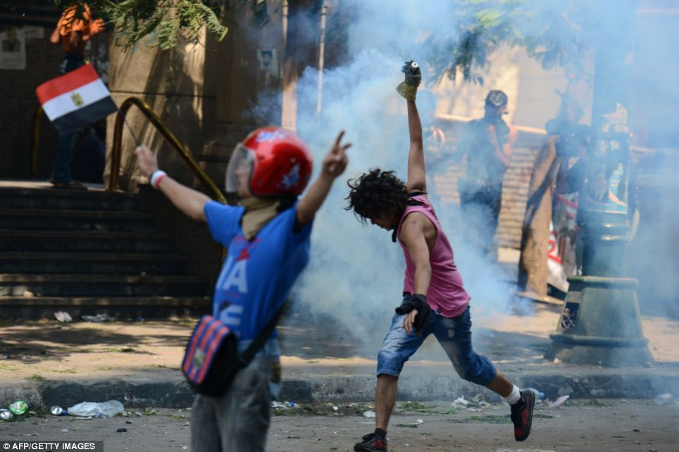 Defiant: Protestors fought back during protests in Cairo, throwing tear gas canisters used to disperse the crowds back at riot police