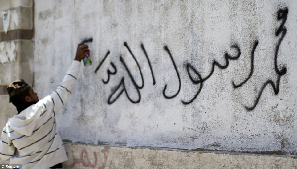 Written on stone: A graffiti artist writes 'Muhammad is the Messenger of Allah!' on a wall