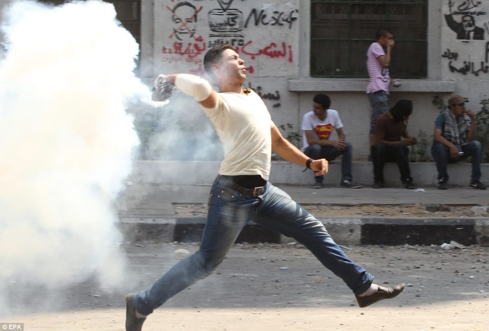 Return fire: An Egyptian protester throws back a tear gas canister towards riot police during clashes near the US embassy in Cairo