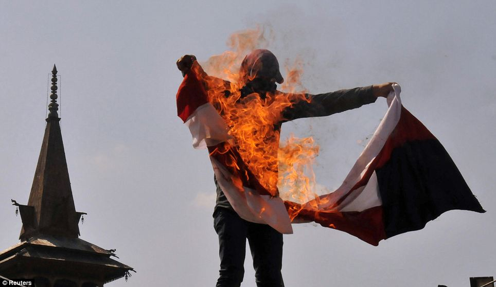 Flag burning: A Kashmiri masked protester holds a burning U.S. flag during a protest against a film the demonstrators consider to be blasphemous to Islam