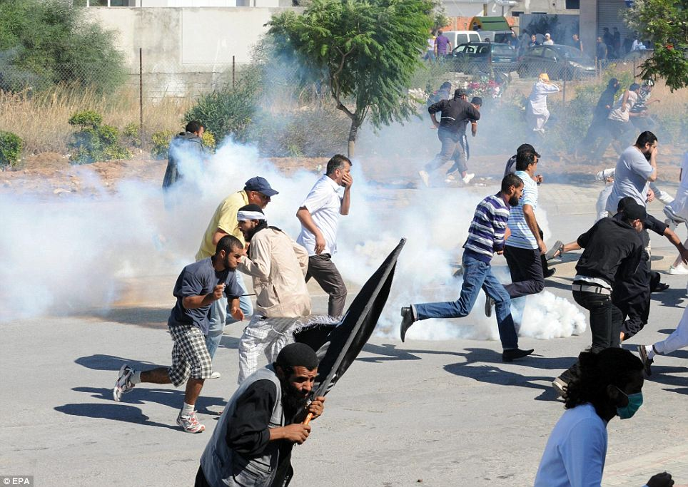 Tunisian demonstrators run after security forces fired tear gas towards them outside the US embassy, in Tunis