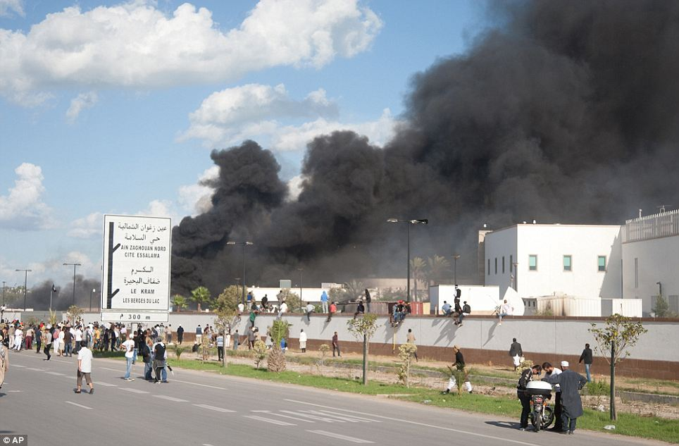 A pall of smoke rises above protesters after they set alight cars in the U.S. embassy parking lot in Tunis