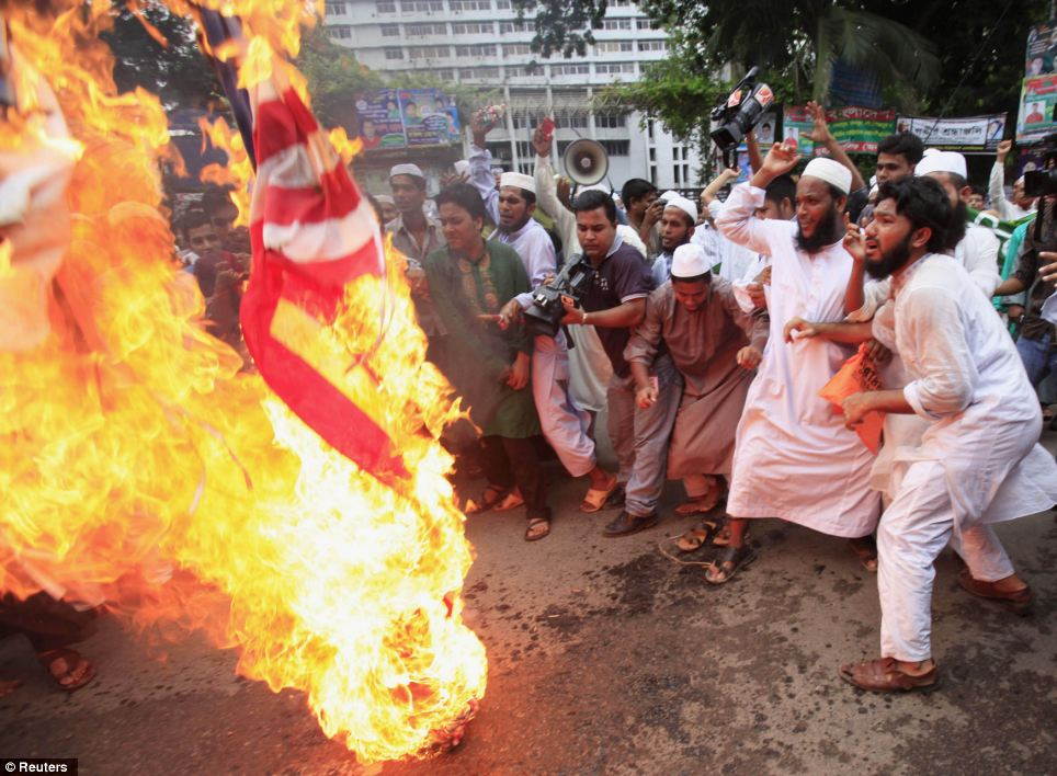Outrage: In Bangladesh, Muslims burn a U.S. flag and an Israeli flag as they shout slogans in front of National Press Club in Dhaka on Friday as part of a protest against the film