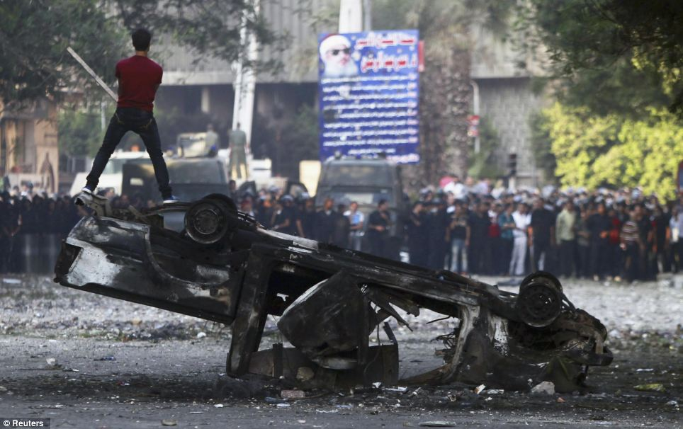 Fired up by the muslim brotherhood and other islamic extremists: In Cairo, a protester shouts slogans as he stands on a burnt car during clashes with riot police along a road leading to the U.S. embassy, near Tahrir Square in Cairo