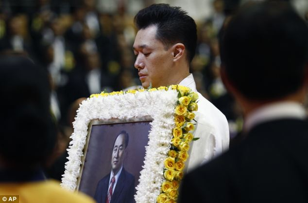 Mourning: A family member carries a portrait of late Rev. Sun Myung Moon - he built a multibillion-dollar business empire stretching from the Korean Peninsula to the United States