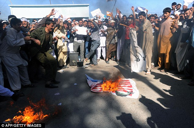 Brimming anger: Afghan demonstrators prepare to torch a U.S. flag during protest in Herat
