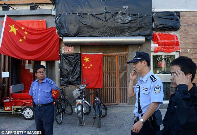 Police walk past a closed Japanese restaurant covered with Chinese national flags as anti-Japanese protests continued outside the Japanese Embassy in Beijing