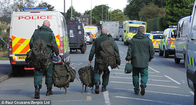 Bringing aid: Emergency service workers carry bags and equipment to the scene of the killings