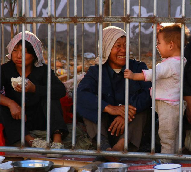 Behind bars: A woman is laughing with a young child inside one of the zoo- like cages where beggars are kept during the temple festival after organisers complained they 'spoil' the celebrations