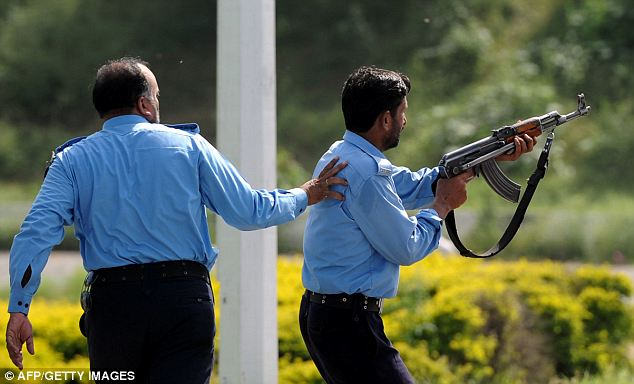 Taking fire: A Pakistani police officer fires into the crowd at an protest in Islamabad on Friday