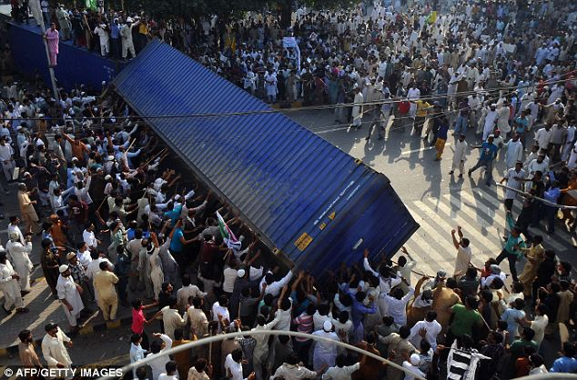 Toppling the barriers: The mass of people worked together to push down the freight containers set up by police