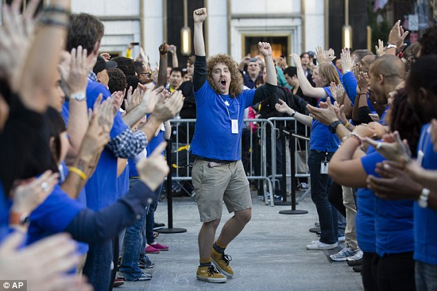 Jubilant: An employee riles up his coworkers outside the Fifth Avenue store to celebrate the new gadget