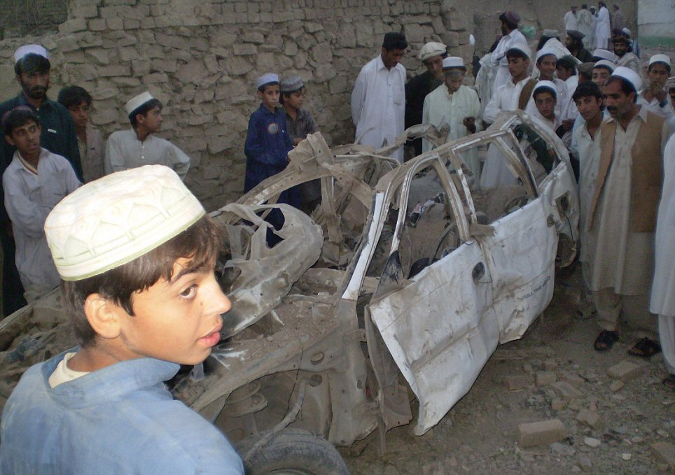 Tribesmen gather near a damaged car outside a house after a missile struck in Dandi Darpakheil village on the outskirts of Miranshah, the main town in the North Waziristan tribal region