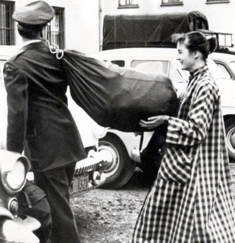 Aid: Elvis gets a helping hand from a young woman as he carries his kit bag in Germany