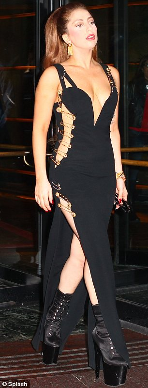 Born to imitate: Lady Gaga was pictured on Tuesday in Milan wearing a black Versace gown held together with gold safety pins identical to the one that Liz Hurley wore in 1994