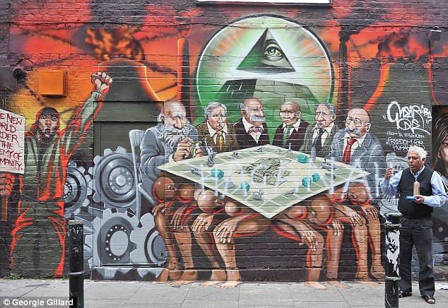 Azmel Hussain, pictured, is defending the artwork which has been painted on his property. He described the wall as showing world leaders playing monopoly on a table held up by tax payers
