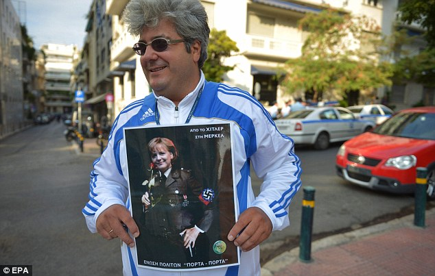 Slur: A man holds a placard saying 'From Hitler to Merkel' in front of the German embassy in Athens