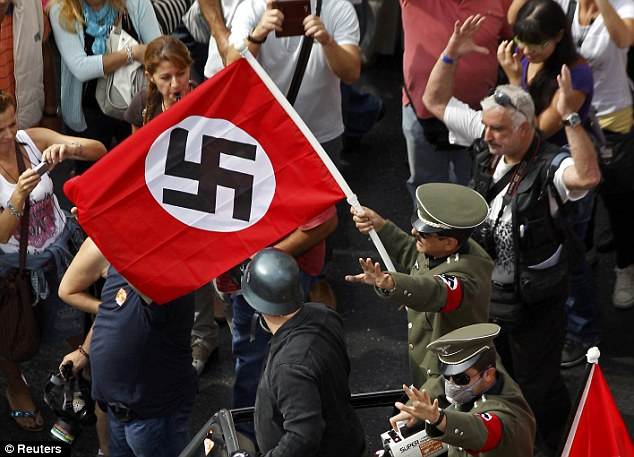 Going to war on austerity: Demonstrators dressed as Nazis wave a swastika flag as they ride in an open-top car in Syntagma Square, Athens